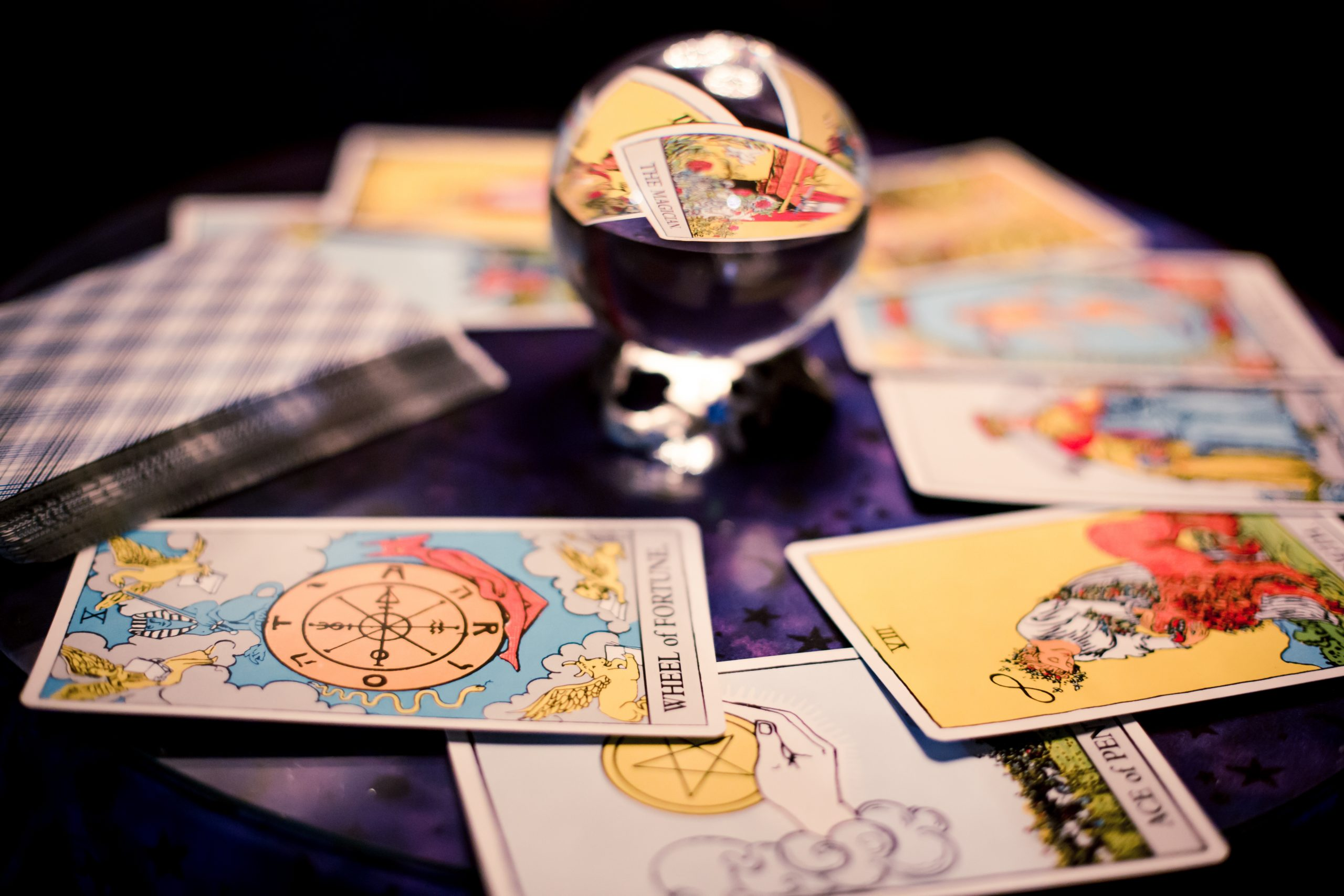 Antique tarot cards spread on a purple table surrounding crystal ball for Halloween